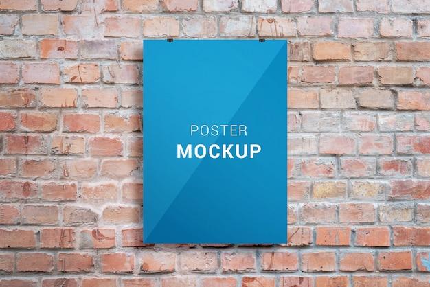 Maqueta de presentación de diseño de carteles. cartel de papel colgado con clips a través de la pared de ladrillo