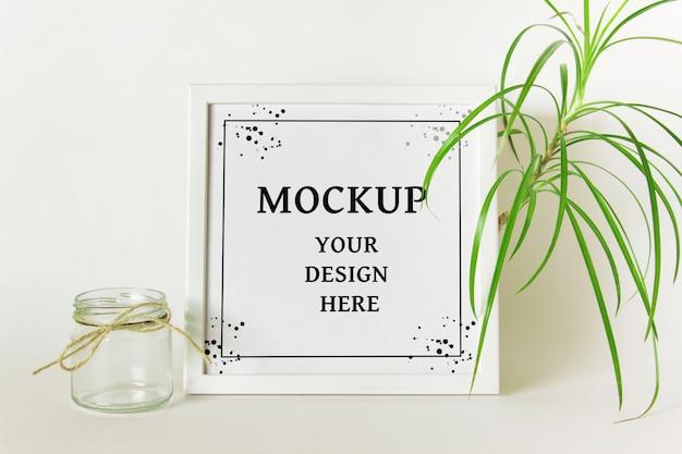 Maqueta psd editable con marco cuadrado blanco, planta verde y frasco de vidrio decorativo vacío