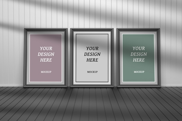 Maqueta psd editable con tres marcos para cuadros en el piso junto a la pared