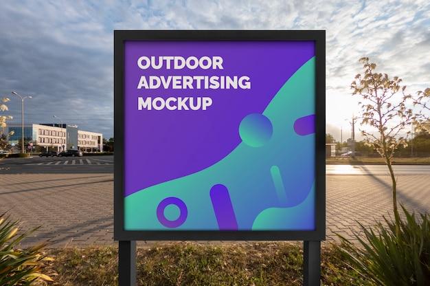 Maqueta de la publicidad de la pancarta al aire libre de la calle de la ciudad en el stand cuadrado negro