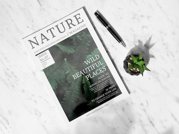 Maqueta de la revista nature al lado de una planta suculenta