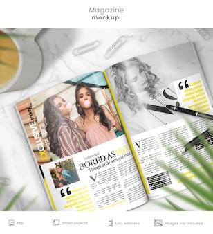 Maqueta de revista de revista abierta sobre mesa de mármol