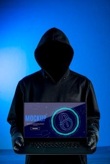 Maqueta de seguridad digital y hombre con capucha.