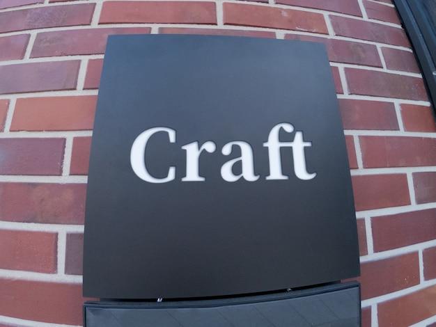 Maqueta de señalización de logotipo cuadrado negro en la pared del edificio de artesanía de ladrillo