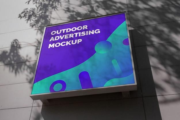 Maqueta de señalización publicitaria cuadrada al aire libre en fachada gris con sombra de árbol