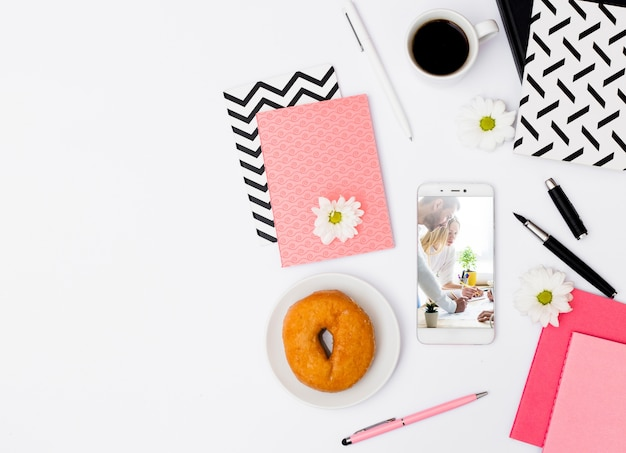Maqueta de smartphone con desayuno en oficina