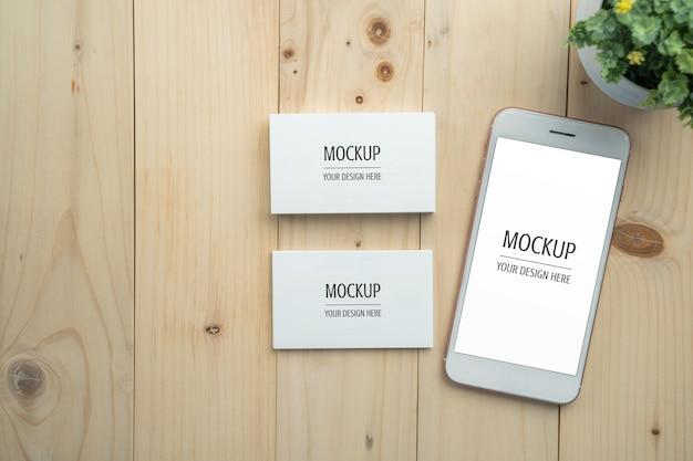 Maqueta de smartphone y tarjeta de visita de pantalla blanca en blanco en mesa de madera