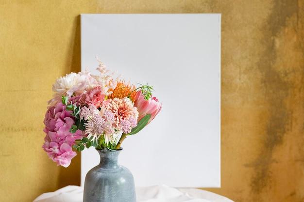 Maqueta de tablero en blanco contra una pared amarilla por un jarrón de flores