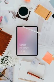 Maqueta de tableta digital en un escritorio desordenado