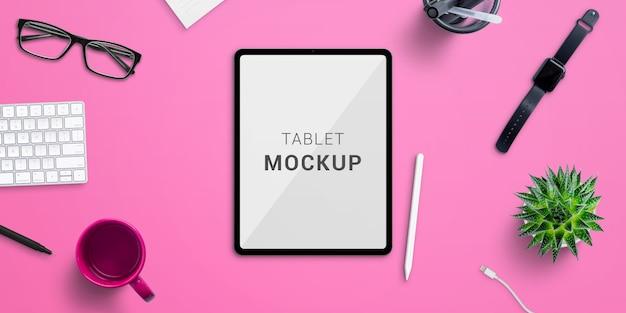 Maqueta de tableta en escritorio de oficina rosa. creador de escenas con capas aisladas. vista superior, composición plana