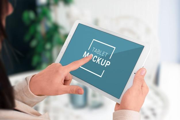 Maqueta de tableta en manos de mujer. mujer sosteniendo moderno en posición horizontal y pantalla táctil con concepto de mano izquierda