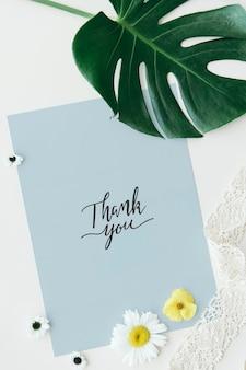 Maqueta de tarjeta azul con decoración de flores