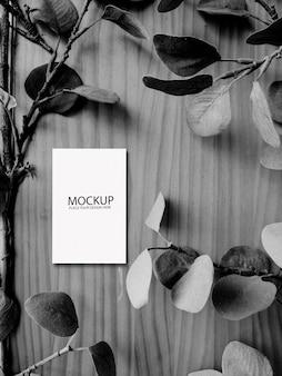Maqueta de tarjeta blanca sobre mesa de madera en blanco y negro