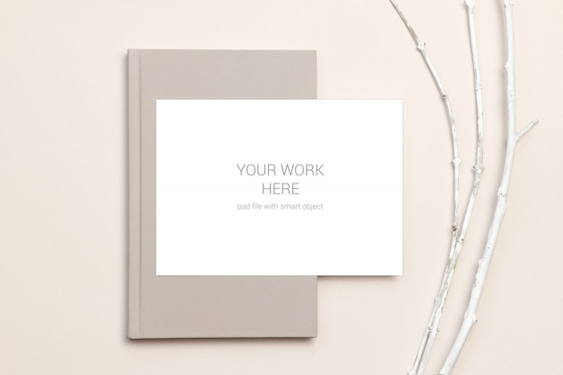 Maqueta de tarjeta en cuaderno y ramas