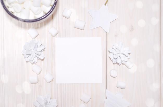 Maqueta de tarjeta cuadrada de navidad con decoraciones blancas en mesa de madera blanca
