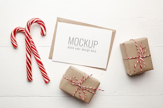 Maqueta de tarjeta de deseos navideños con cajas de regalo y bastones de caramelo