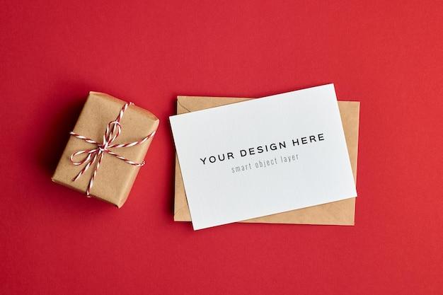 Maqueta de tarjeta del día de san valentín con caja de regalo sobre fondo de papel rojo