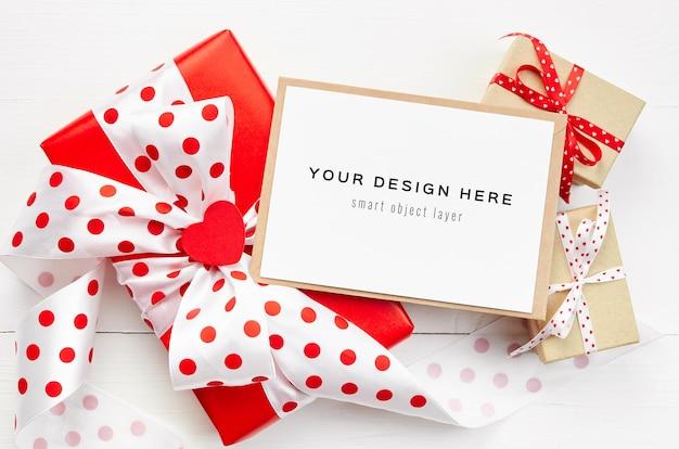 Maqueta de tarjeta del día de san valentín con cajas de regalo sobre fondo blanco.