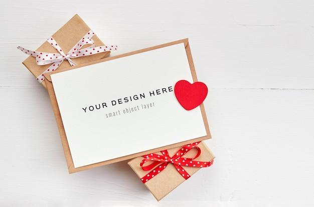 Maqueta de tarjeta del día de san valentín con corazón rojo y cajas de regalo sobre fondo blanco.