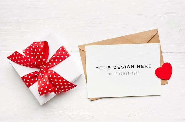 Maqueta de tarjeta del día de san valentín con sobre y caja de regalo sobre fondo blanco.