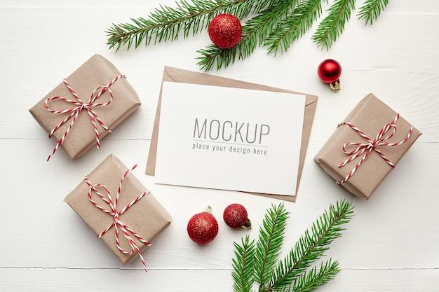 Maqueta de tarjeta de felicitación con adornos navideños y ramas de abeto