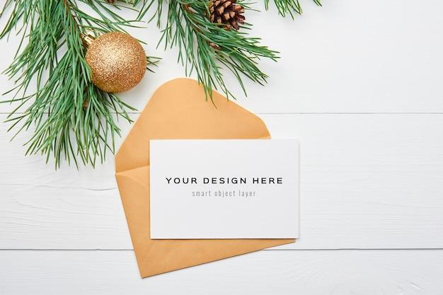 Maqueta de tarjeta de felicitación con adornos navideños sobre fondo blanco de madera