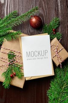 Maqueta de tarjeta de felicitación con caja de regalo, adornos navideños rojos y ramas de abeto