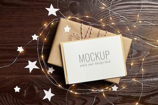Maqueta de tarjeta de felicitación con caja de regalo y luces navideñas en mesa de madera