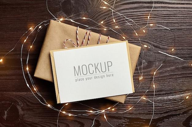 Maqueta de tarjeta de felicitación con caja de regalo y luces navideñas sobre fondo de madera