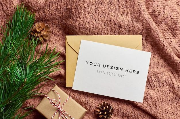 Maqueta de tarjeta de felicitación con caja de regalo de navidad y rama de pino