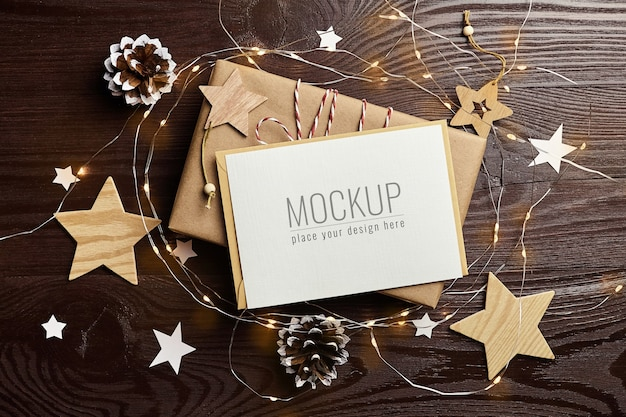 Maqueta de tarjeta de felicitación con caja de regalo, piñas, adornos de madera y luces navideñas