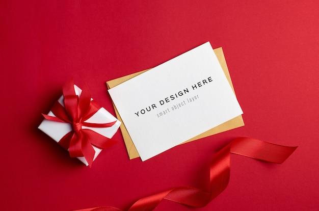 Maqueta de tarjeta de felicitación con caja de regalo sobre fondo rojo