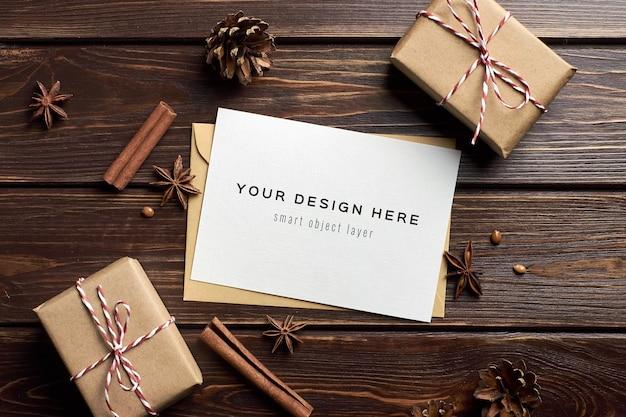 Maqueta de tarjeta de felicitación con cajas de regalo de navidad, naranjas secas y especias en mesa de madera