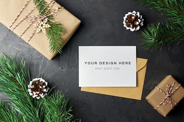 Maqueta de tarjeta de felicitación con cajas de regalo de navidad y ramas y conos de pino