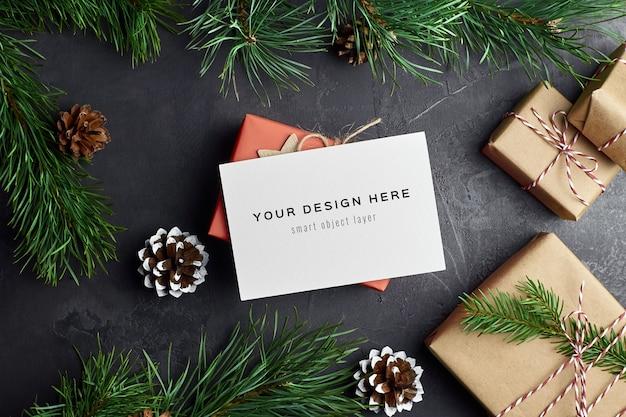 Maqueta de tarjeta de felicitación con cajas de regalo de navidad y ramas de pino y conos en la oscuridad