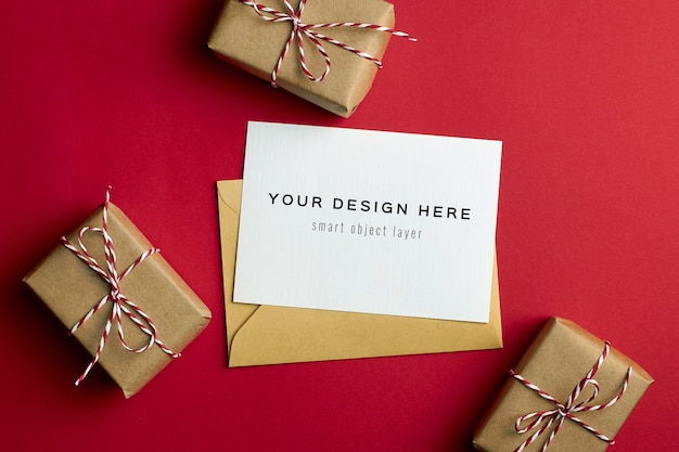 Maqueta de tarjeta de felicitación con cajas de regalo de navidad sobre fondo de papel rojo