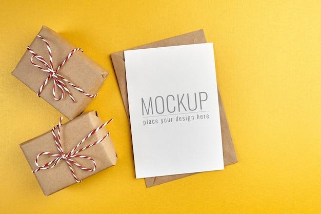 Maqueta de tarjeta de felicitación con cajas de regalo sobre fondo de papel dorado