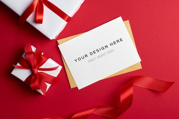 Maqueta de tarjeta de felicitación con cajas de regalo sobre fondo rojo.