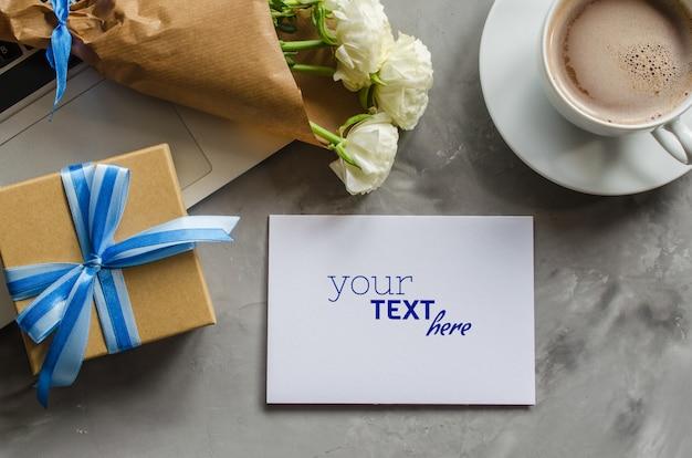 Maqueta de tarjeta de felicitación con computadora portátil, caja de regalo, café de la mañana y flores.