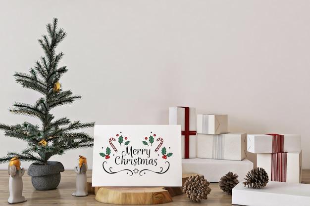 Maqueta de tarjeta de felicitación de feliz navidad con árbol de navidad, decoración y regalos