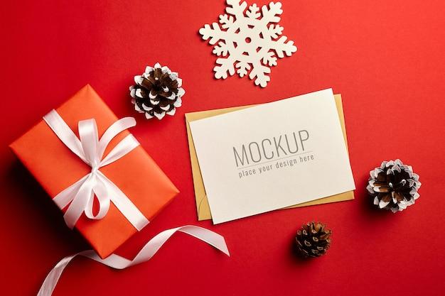Maqueta de tarjeta de felicitación de navidad con caja de regalo y adornos sobre fondo rojo.