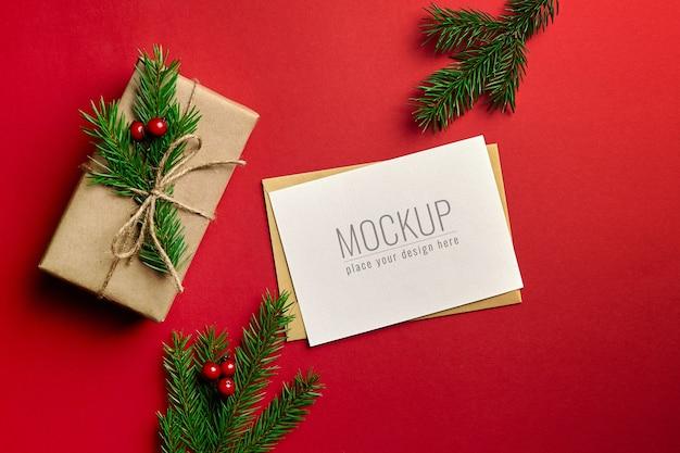 Maqueta de tarjeta de felicitación de navidad con caja de regalo decorada y ramas de abeto sobre fondo rojo.