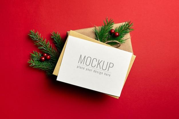 Maqueta de tarjeta de felicitación de navidad con caja de regalo decorada sobre fondo rojo.