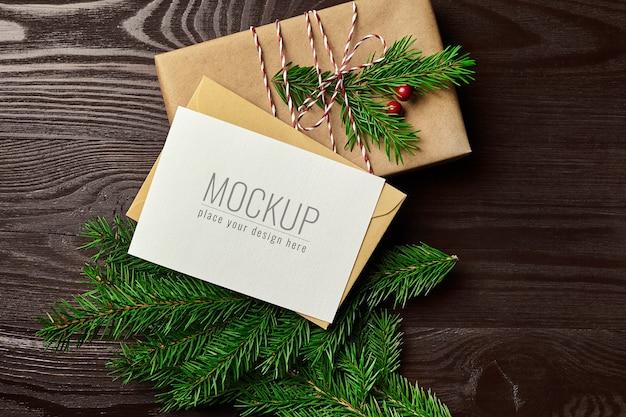 Maqueta de tarjeta de felicitación de navidad con caja de regalo y ramas de abeto en mesa de madera