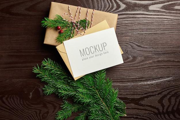 Maqueta de tarjeta de felicitación de navidad con caja de regalo y ramas de abeto sobre fondo de madera