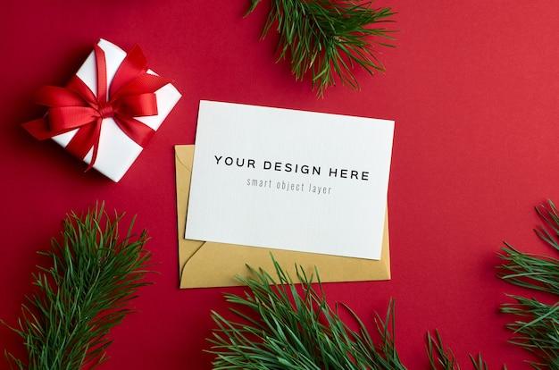 Maqueta de tarjeta de felicitación de navidad con caja de regalo y ramas de pino en rojo