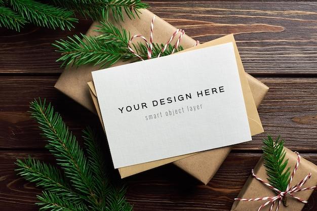 Maqueta de tarjeta de felicitación de navidad con cajas de regalo de navidad y ramas de abeto
