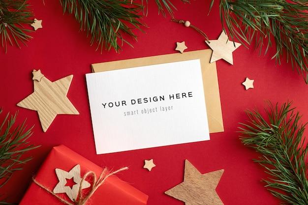 Maqueta de tarjeta de felicitación de navidad con cajas de regalo y ramas de pino en rojo