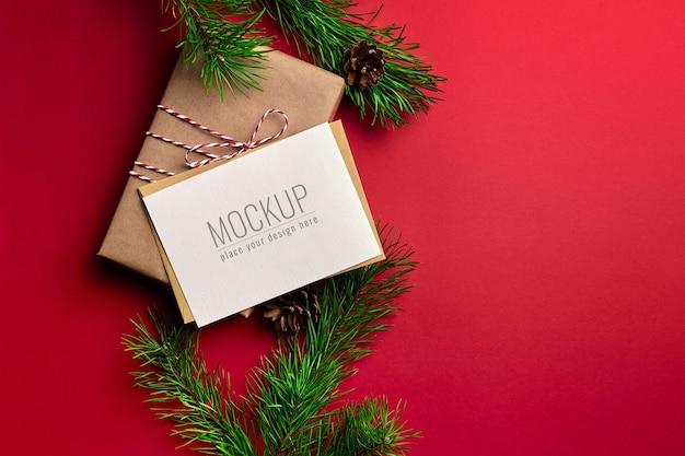 Maqueta de tarjeta de felicitación de navidad con cajas de regalo y ramas de pino sobre fondo rojo.