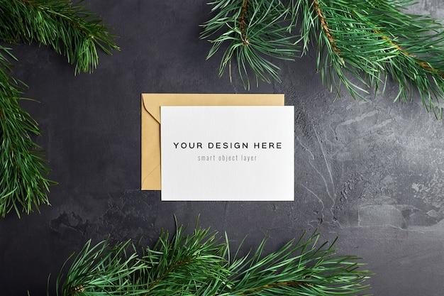 Maqueta de tarjeta de felicitación de navidad con ramas de pino sobre fondo oscuro